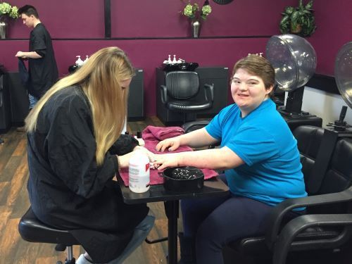 A cosmetology student completing a manicure for another student