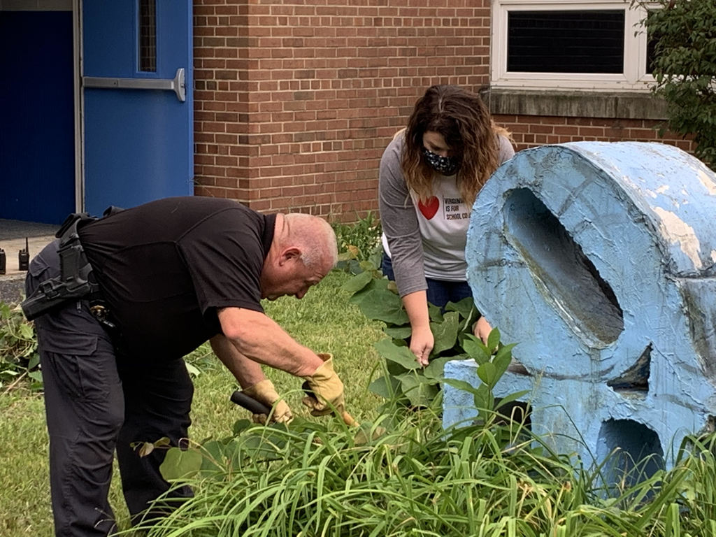 SRO Dinky Conley and School Counselor, Casey Owens weeding the memorial garden