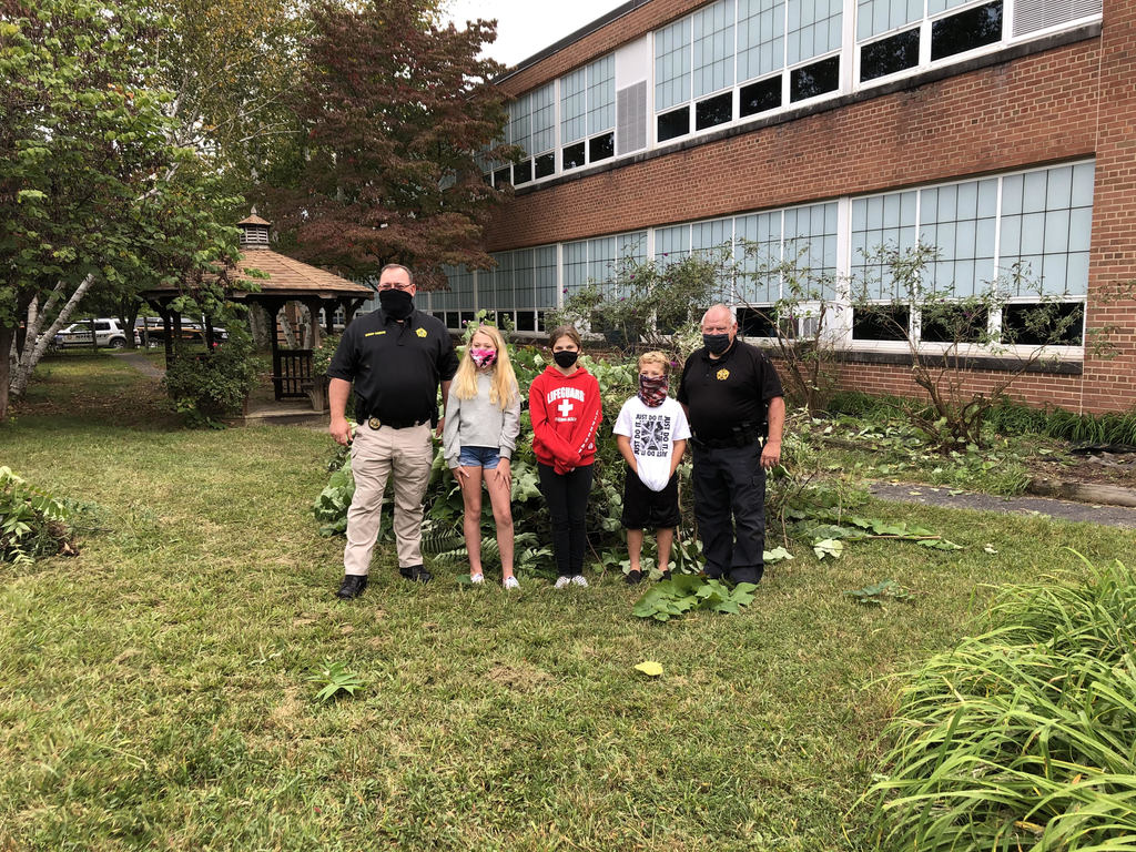 Sheriff Chad Cubbage, SRO Dinky Conley and 7th grade students  helping to weed the memorial garden at PCMS